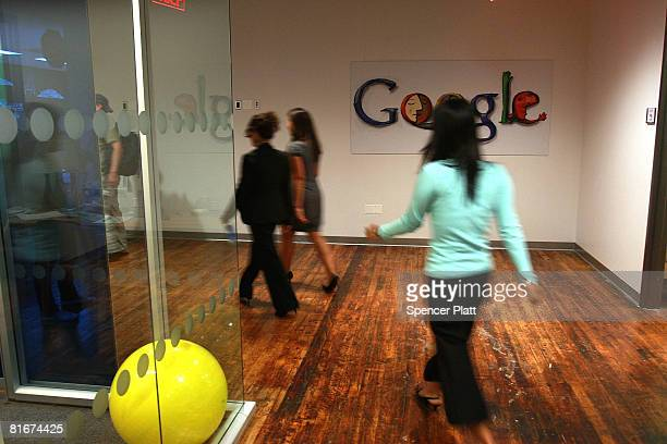 Employees of Google walk down a hallway at the internet company's new office space inside historic Chelsea Market June 23 2008 in New York City The...