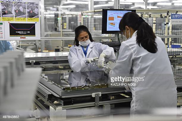 Employees of Japanese electronics giant Sharp work on the AQUOS 4K television assembly line at the company's Tochigi Plant in Yaita Tochigi...