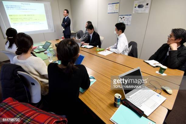 Employees of Japan's brewing and distilling company group Suntory attend a meeting at their office in Tokyo on February 24 2017 Welcome to Premium...