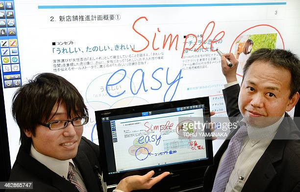 Employees of Japan's Sharp Corporation demonstrate how to use a new 70inch touchscreen display called 'Big Pad PNL703A' and a 156inch tablet 'IGZO...