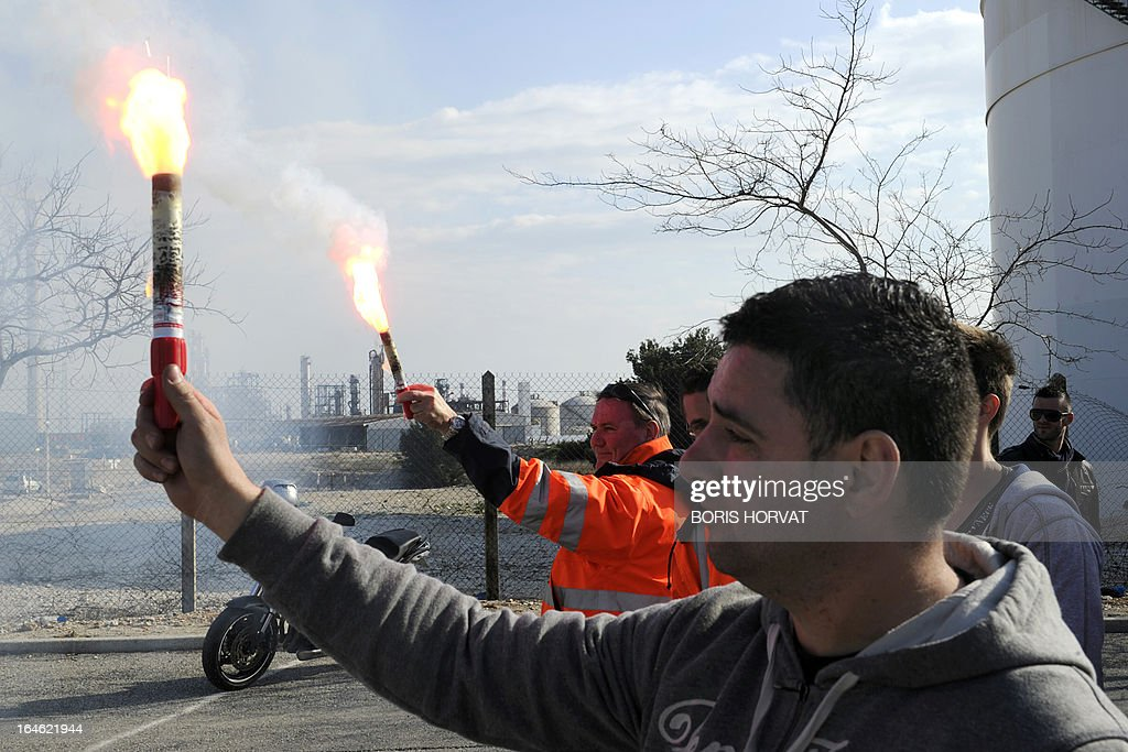Employees of Kem One, a French company specialized in chlorochemicals and vinyl products, hold warning lights as they block the access to their company in Lavera, southern France, on March 25, 2013 after French unions announced the company's cessation of payments. 350 jobs could be cut on the Lavera site. AFP PHOTO / BORIS HORVAT