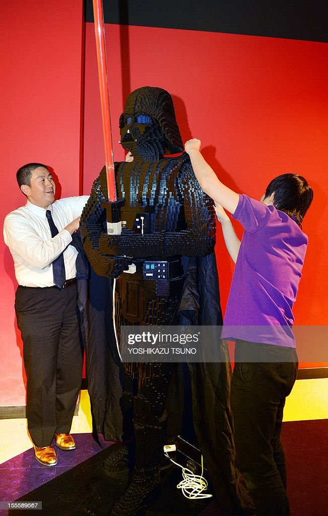 Employees of Lego Japan put a robe on some 50,000 Lego blocks of Darth Vader, a character of US movie Star Wars in Tokyo on November 5, 2012 at the Legoland Discovery Center Tokyo. The characters of the Star Wars saga, set to be revived from 2015 under new owners Disney, will be displayed from November 6. AFP PHOTO / Yoshikazu TSUNO