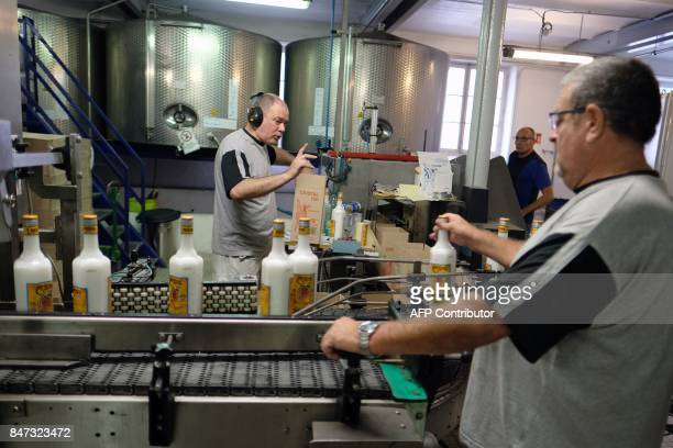 Employees of 'Liminana' company that manufactures Pastis controls bottles on an assembly line before filling at the company's plant in Marseille...
