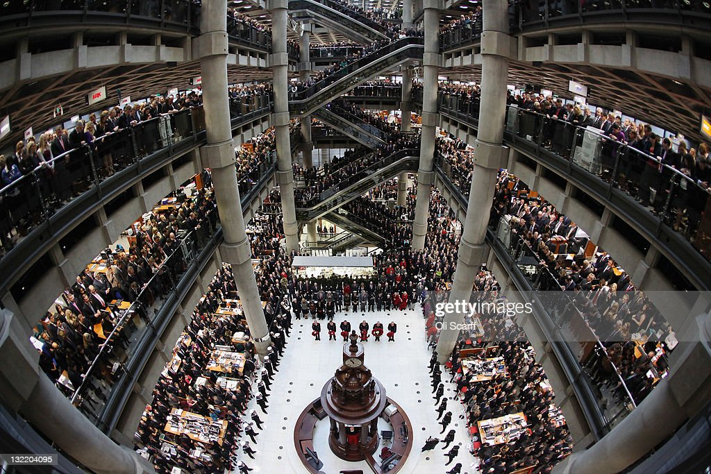 Employees of Lloyd's observe a two minute silence on Armistice Day in the Underwriting Room of Lloyd's Building on November 11, 2011 in London, England. The annual Remembrance Day service honours those who have lost their lives during times of war. The service at Lloyd's is observed with the ringing of the Lutine Bell, the laying of wreaths before the Book of Remembrance and a two minute silence.