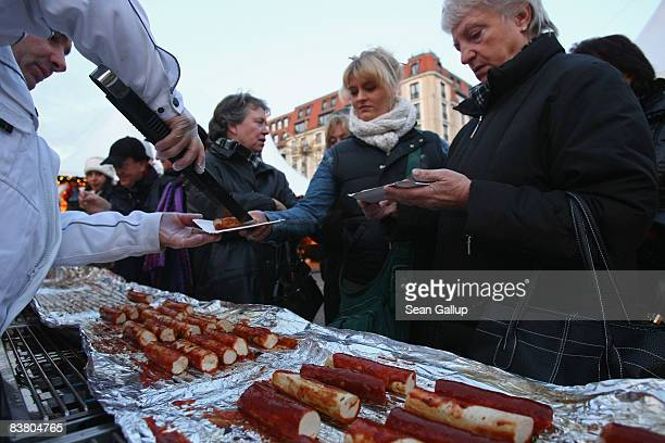 Employees of Maximilian meat specialties give away free portions of what Maximilian head Leo Friedrich claims is the world's longest currywurst at...