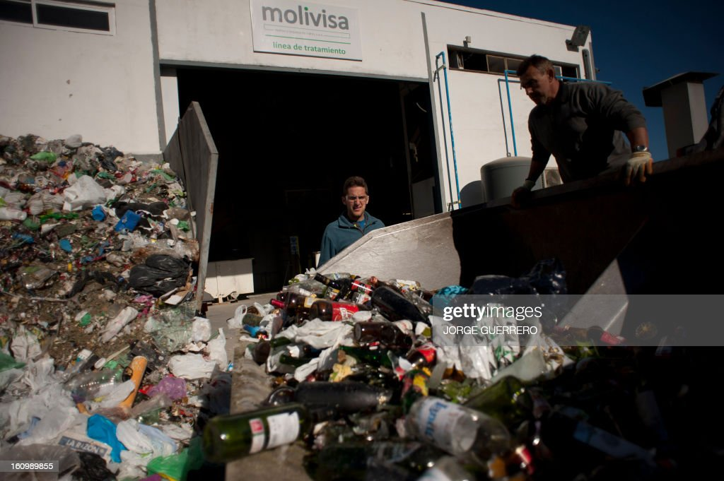 Employees of Movilsa separate plastic waste from used glass bottles at the Movilsa glass recycling center in Alhauri­n de la Torre, near Malaga, on February 8, 2013.
