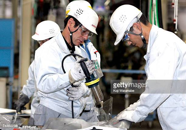 Employees of Nissan Motor Company work on the assembly line at Nissan's Global Production Engineering Center on May 29 2007 in Zama Japan The GPEC in...