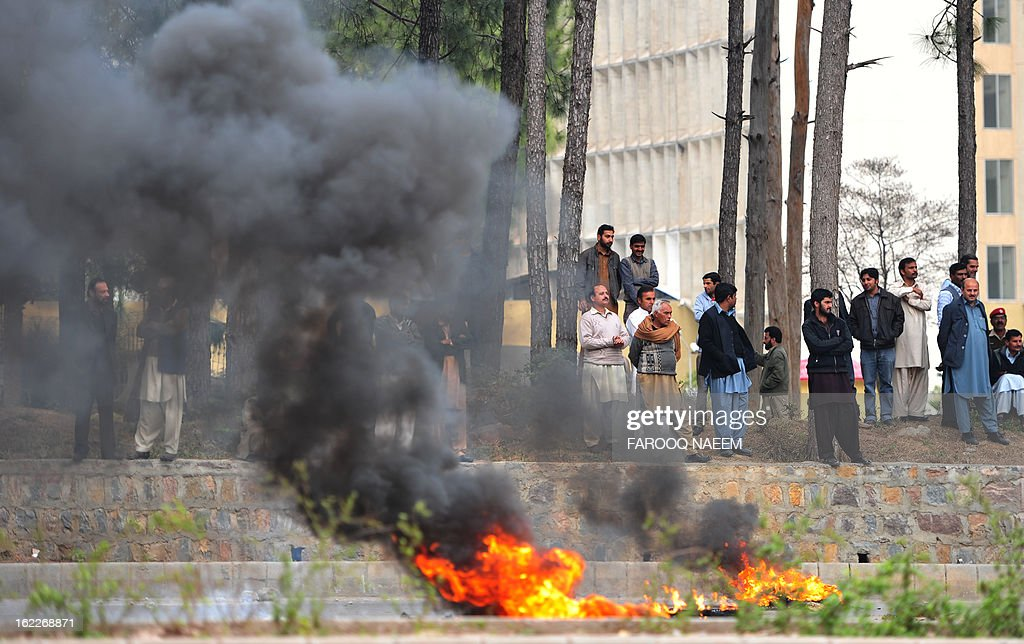 Employees of Pakistani government-operated national news agency Associated Press of Pakistan (APP) burn tyres in a protest on a street in Islamabad on February 21, 2013. Employees of APP staged a protest against non-payment of arrears and the stoppage of various allowances for the past two years. AFP PHOTO/Farooq NAEEM