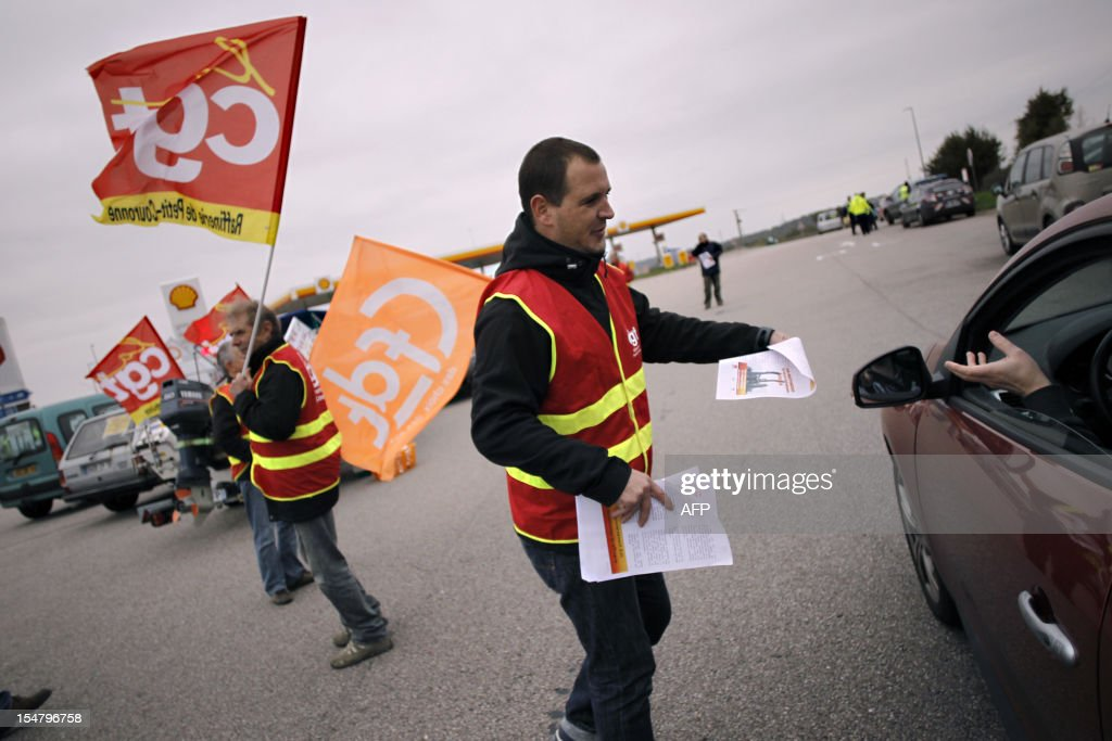 Employees of Petroplus oil refinery distribute leaflets at a gas station of the A13 highway after blocking the road on October 26, 2012 in the highway, 10km from Rouen, northwestern France. The court in Rouen ordered the liquidation of Petroplus on October 16, 2012, despite two offers for the site that employs 470 people. The court left open the possibility for other bidders to come forward by November 5 however, amid widespread anger among the refinery's workers.