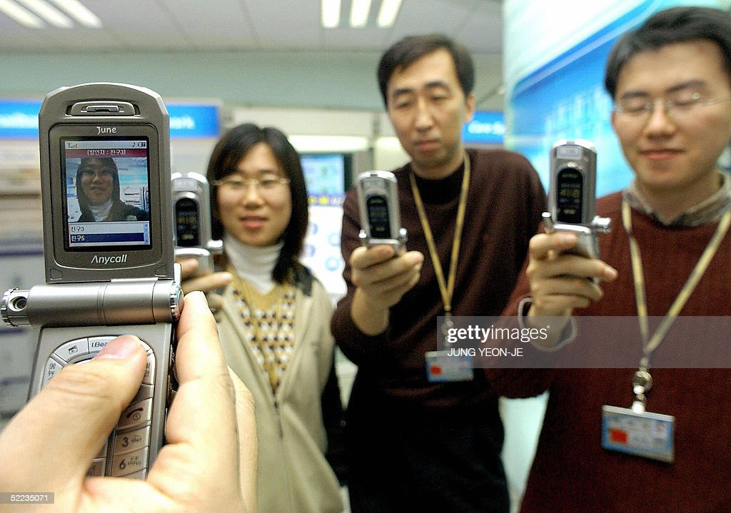 Employees of Samsung Electronics demonstrate one to multi-user video conferencing on mobile phones at the Telecommunication Network R&D Center in Suwon, south of Seoul, 24 February 2005. Samsung Electronics announced the development of a working PTA (Push-to-All) solution. This total mobile communications solution incorporates the existing PTT (Push-to-Talk) one to multi-user voice technology with the one to multi-user video conferencing ability of PTV (Push-to-View) and multimedia file sharing function of PTD (Push-to Data). AFP PHOTO/JUNG YEON-JE