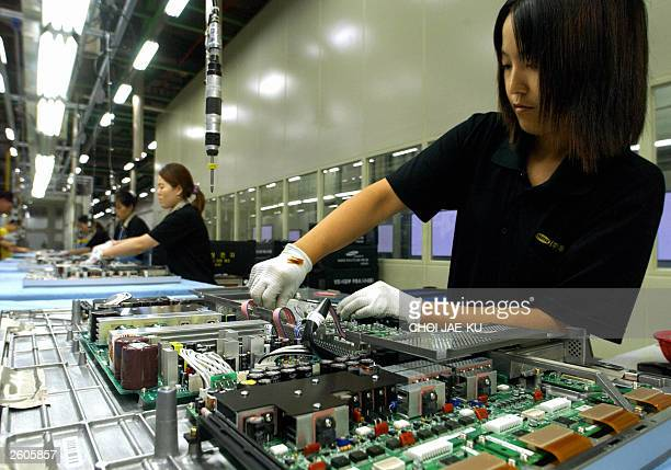 Employees of Samsung Electronics set up large LCD TV on a production line at Samsung Electronics factory in Suwon 07 August 2003 South Korea's...