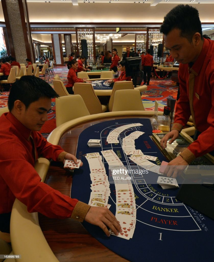 Employees of Solaire Manila Resorts and casino check gaming cards during media day inside the casino in Manila on March 14, 2013, ahead of its opening on March 16. The Philippines makes its biggest bet this weekend in a high-stakes bid to join the world's elite gaming destinations, with the launch of a $1.2-billion casino on Manila Bay.Solaire Manila Resorts is the first of four enormous entertainment venues slated to rise over a giant chunk of prime, reclaimed land that industry and government leaders expect will attract millions of cashed-up Asian tourists. AFP PHOTO/TED ALJIBE