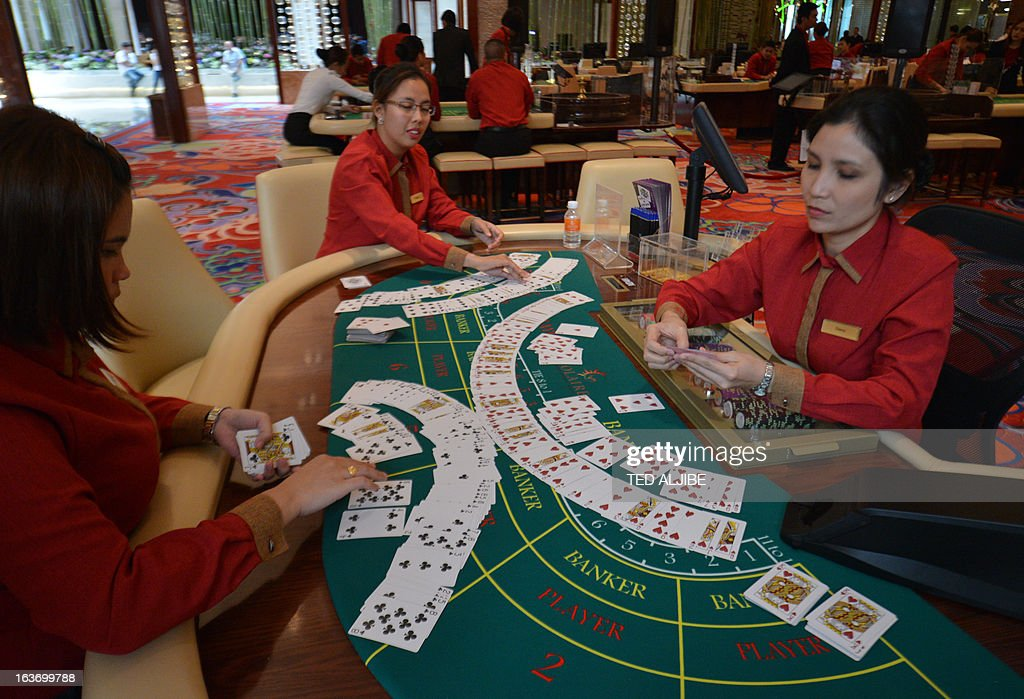 Employees of Solaire Manila Resorts and casino check gaming cards during media day inside the casino in Manila on March 14, 2013, ahead of its opening on March 16. The Philippines makes its biggest bet this weekend in a high-stakes bid to join the world's elite gaming destinations, with the launch of a $1.2-billion casino on Manila Bay.Solaire Manila Resorts is the first of four enormous entertainment venues slated to rise over a giant chunk of prime, reclaimed land that industry and government leaders expect will attract millions of cashed-up Asian tourists.