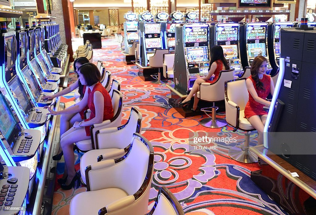 Employees of Solaire Manila Resorts and casino pose for photo next to gaming machines inside the casino in Manila on March 14, 2013, ahead of its opening on March 16. The Philippines makes its biggest bet this weekend in a high-stakes bid to join the world's elite gaming destinations, with the launch of a $1.2-billion casino on Manila Bay.Solaire Manila Resorts is the first of four enormous entertainment venues slated to rise over a giant chunk of prime, reclaimed land that industry and government leaders expect will attract millions of cashed-up Asian tourists.