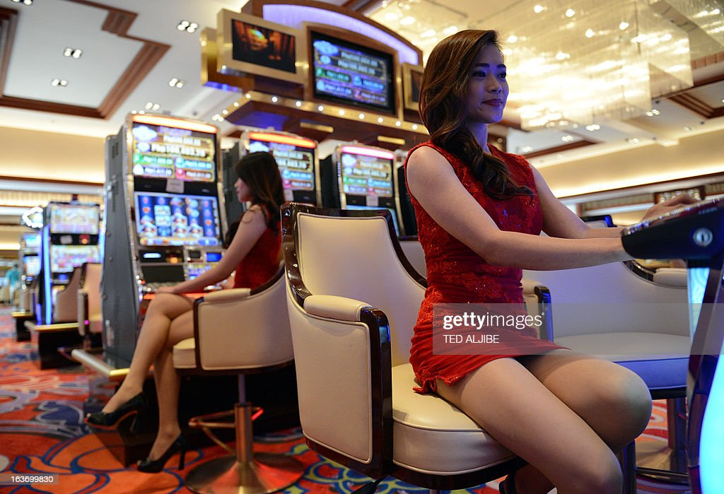 Employees of Solaire Manila Resorts and casino pose for photo next to gaming machines inside the casino in Manila on March 14, 2013, ahead of its opening on March 16. The Philippines makes its biggest bet this weekend in a high-stakes bid to join the world's elite gaming destinations, with the launch of a $1.2-billion casino on Manila Bay.Solaire Manila Resorts is the first of four enormous entertainment venues slated to rise over a giant chunk of prime, reclaimed land that industry and government leaders expect will attract millions of cashed-up Asian tourists. AFP PHOTO/TED ALJIBE
