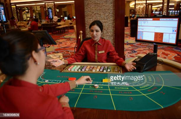 Employees of Solaire Manila Resorts and casino simulate baccarat game during media day inside the casino in Manila on March 14 ahead of its opening...