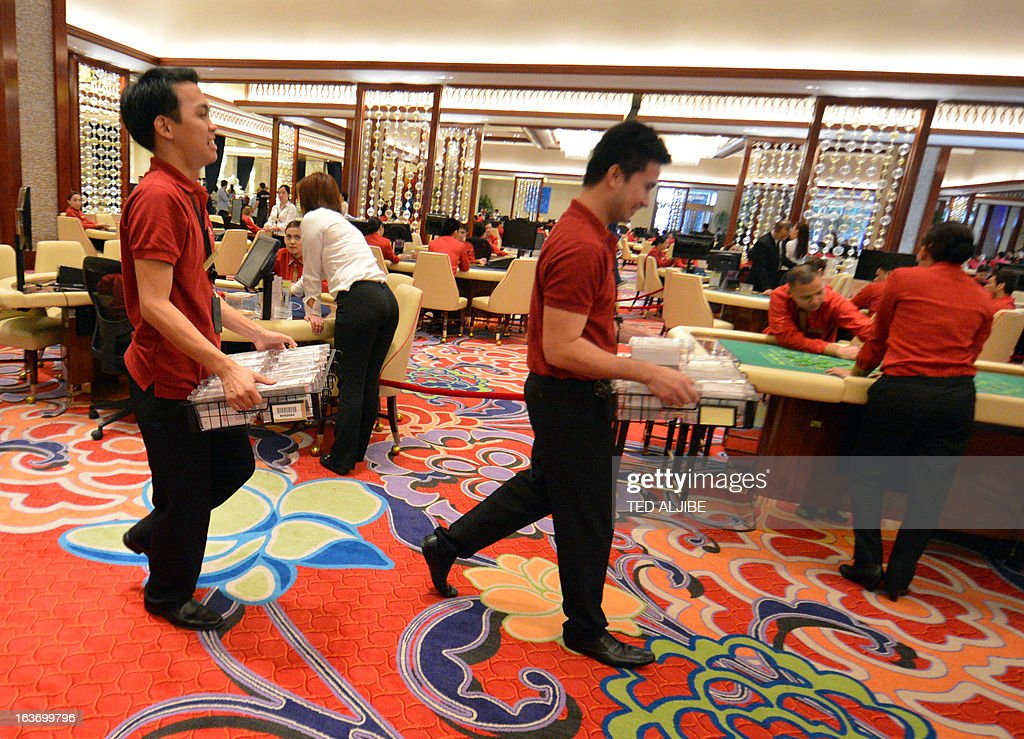 Employees of Solaire Resorts and casino, carry gaming cards during a dry run at the casino in Manila on March 14, 2013, ahead of its opening on March 16. The Philippines makes its biggest bet this weekend in a high-stakes bid to join the world's elite gaming destinations, with the launch of a $1.2-billion casino on Manila Bay.Solaire Manila Resorts is the first of four enormous entertainment venues slated to rise over a giant chunk of prime, reclaimed land that industry and government leaders expect will attract millions of cashed-up Asian tourists.