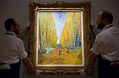 Employees of Sotheby's auction house pose with French artist Vincent van Gogh's L'Allee des Alyscamps painted in 1888 which is estimated to sell for...