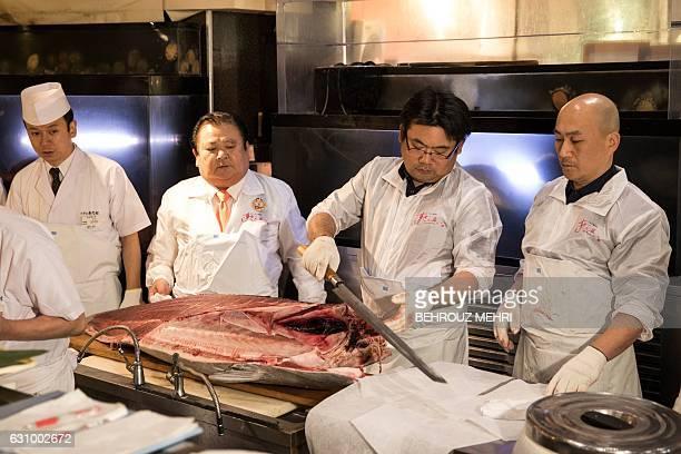 Employees of sushi restaurant chain SushiZanmai prepare a 212kilogram bluefin tuna at their restaurant near the Tsukiji fish market in Tokyo on...