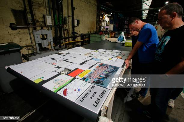 Employees of the automotive supplier GMS Industry where around 280 jobs are on the line look at drawings and message left for them at the GMS plant...