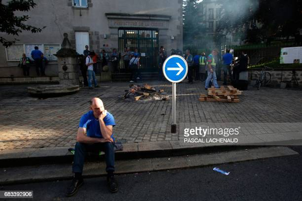 Employees of the automotive supplier Industry in La Souterraine look on after setting wood on fire outside the prefecture of Gueret on May 15 2017...