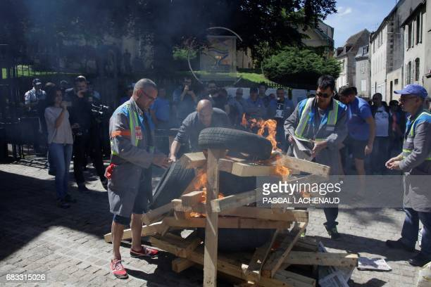 Employees of the automotive supplier Industry in La Souterraine set wood on fire outside the prefecture of Gueret on May 15 2017 during a meeting...