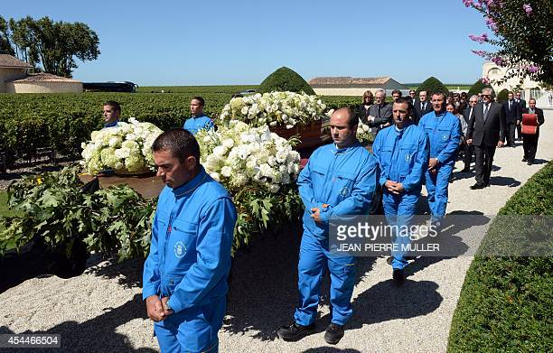 Employees of the Chateau Mouton Rothschild and relatives walk next to the coffin carrying the body of baroness Philippine de Rothschild pulled by a...