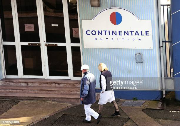 Employees of the Continentale Nutrition factory in BoulognesurMer walk past a company sign near the entrance on February 27 2014 One of the two...