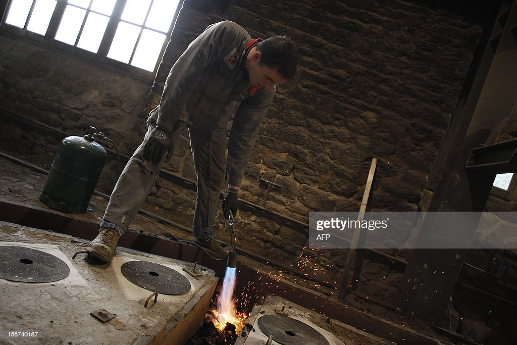 Employees of the Cornille-Havard foundry in Villedieu-les-Poeles look at bronze flowing in the small channels during the melting of two Notre-Dame de Paris cathedral's bells on November 19, 2012. Four bells have to be renovated and five others made at the foundry for the celebration of the cathedral's 850th anniversary in 2013. The nine bells will join the tenor bell 'Emmanuel' known as the 'Bourdon' to re-create the original set used before the French Revolution (1789). TRIBALLEAU