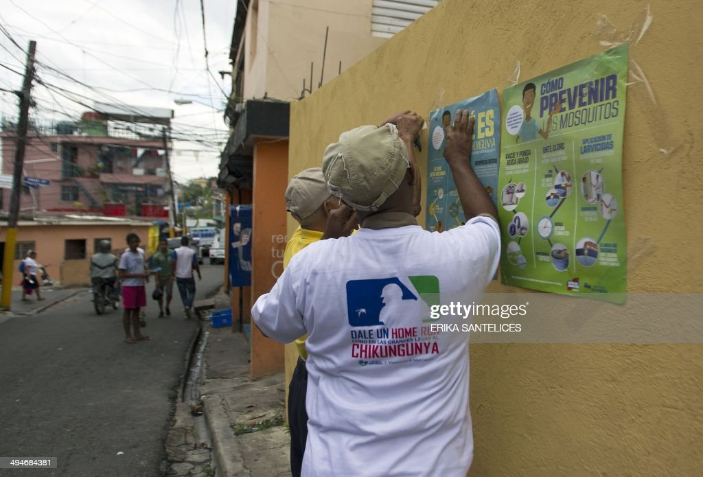 Employees of the Dominican Ministry of Public Health stick posters on a wall during an information campaign to prevent the spread of the mosquito which transmits the Chikungunya virus, in the district of 'La Agustinita', in Santo Domingo, on May 30, 2014.