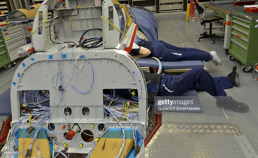 Employees of the EADS company Cassidian work on the assembling of an Eurofighter plane for the German Air Force at the Cassidian production line in Manching, southern Germany, on February 28, 2013. AFP PHOTO / GUENTER SCHIFFMANN