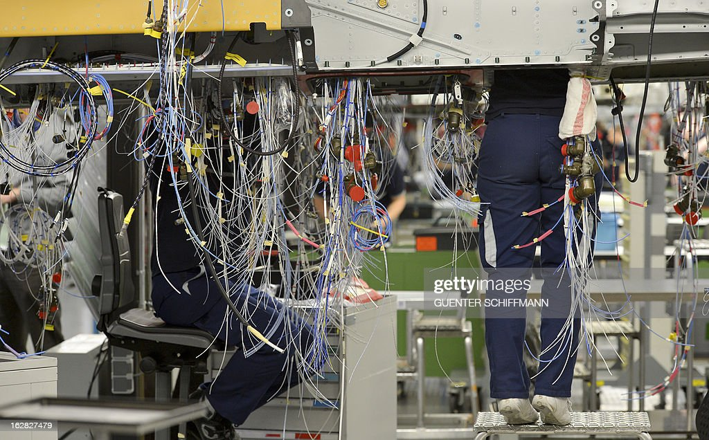 Employees of the EADS company Cassidian work on the cabling at the center fuselage as they assemble an Eurofighter plane for the German Air Force at the Cassidian production line in Manching, southern Germany, on February 28, 2013.