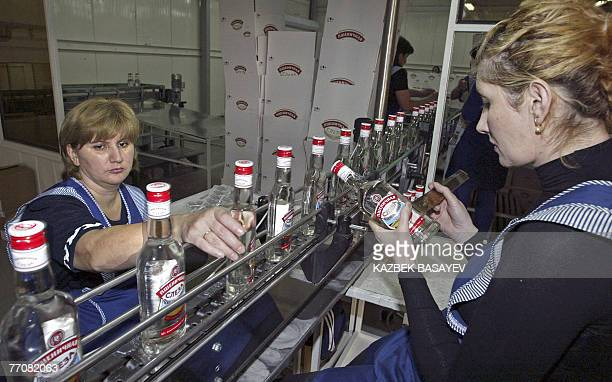 Employees of the 'FayurSoyuz' vodka distillery control a production in the finished commodity department of the factory 28 September 2007 in Beslan...