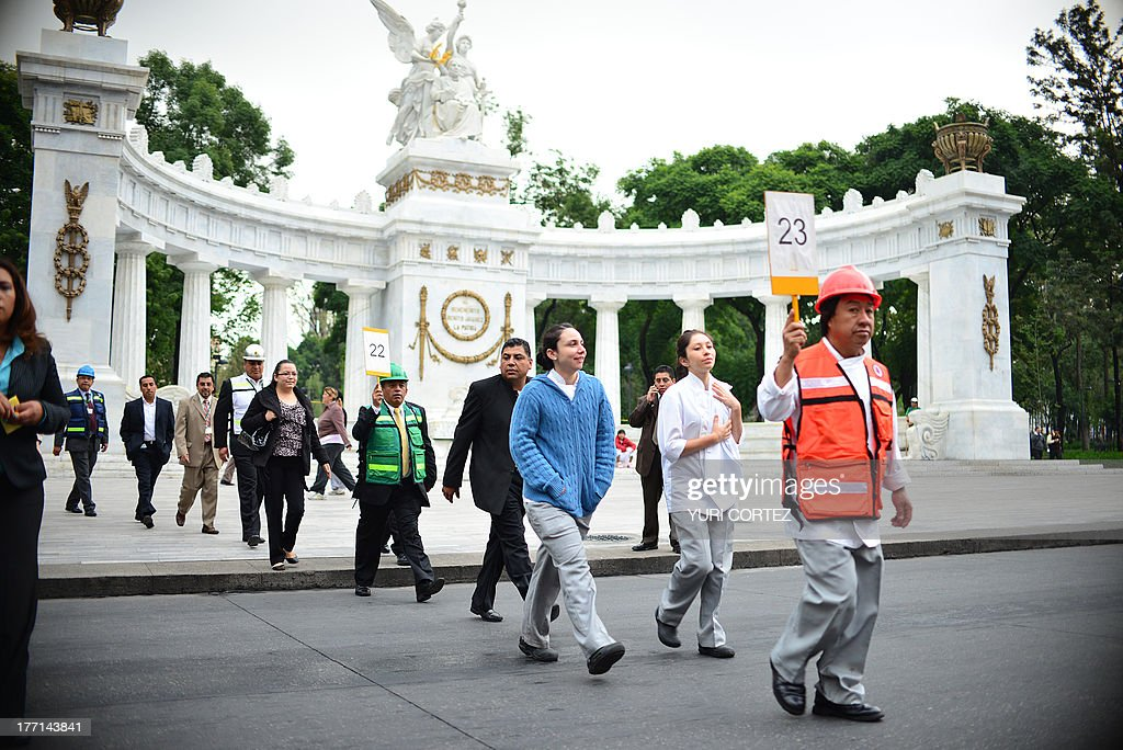 Employees of the Foreign Ministry evacuate after a 6.0 magnitude earthquake shook Mexico City on August 21, 2013. A strong 6.0 magnitude earthquake and an aftershock rattled Mexico on Wednesday, causing evacuations of buildings in the capital and hotels in the Pacific resort of Acapulco. The quake's epicenter has been located 17 km west of the town of San Marcos in the southern state of Guerrero, the National Seismology Center said. A 5.62-magnitude aftershock was reported 20 minutes later 14 km northeast of Acapulco, where rocks from a hill rolled into a street and some hotel facades showed cracks while tourists poured into the streets. AFP PHOTO / Yuri CORTEZ
