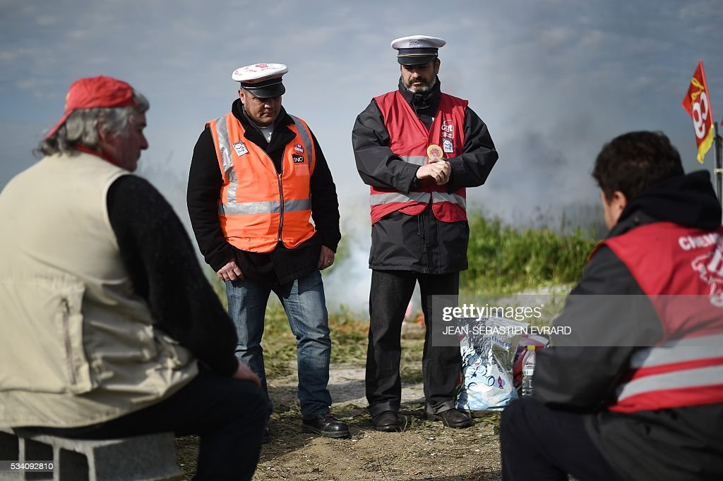 Employees of the France's national state-owned railway company (SNCF) block the access to an oil depot near the Total refinery of Donges, western France, on May 25, 2016 to protest against the government's planned labour law reforms. France has been using strategic fuel reserves for two days in the face of widespread blockades of oil depots by union activists, the head of the oil industry federation said on May 25, 2016. / AFP / JEAN