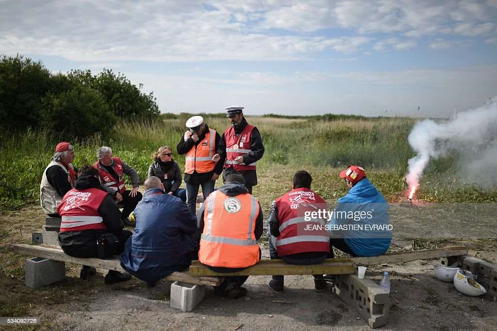 Employees of the France's national state-owned railway company (SNCF) sit as they block the access to an oil depot near the Total refinery of Donges, western France, on May 25, 2016 to protest against the government's planned labour law reforms. France has been using strategic fuel reserves for two days in the face of widespread blockades of oil depots by union activists, the head of the oil industry federation said on May 25, 2016. / AFP / JEAN