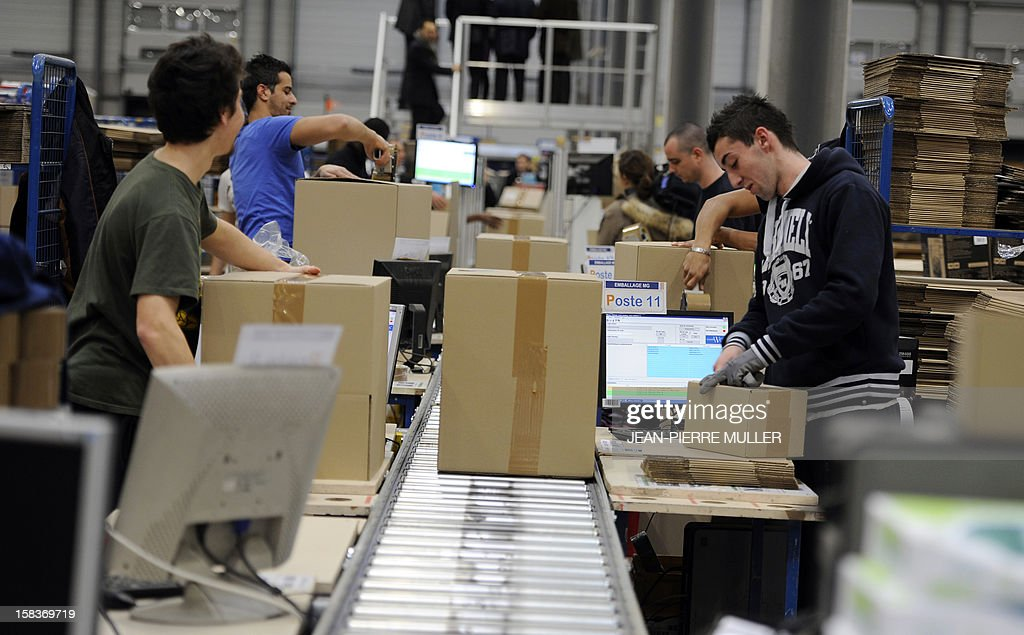 Employees of the French 'C Discount' online trade company checks barcodes as he prepares items in a store in Cestas, southwestern France, on December 14, 2012.