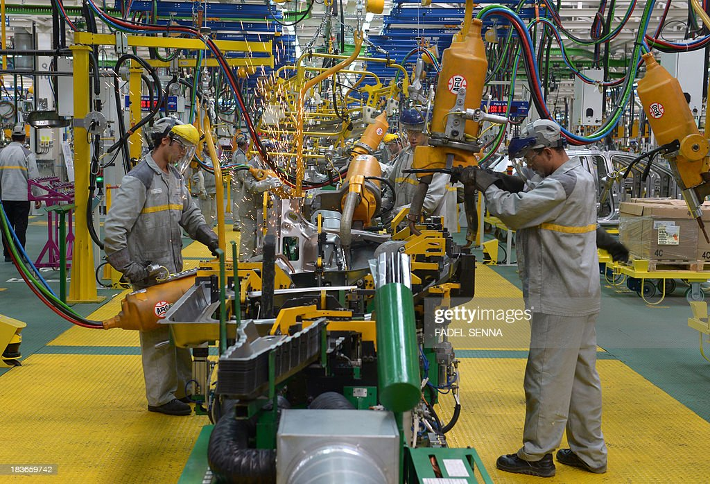 Employees of the French Renault group in Morocco work on a production line at the new second phase of the Renault factory in Tangier on October 8, 2013. This second unit inaugurated on October 8 which will oversee the production of the Dacio Sandero car, will allow the French manufacturer to double its production, to reach 340,000 vehicles per year in 2014, which will make Renault Tangier 'the biggest factory' of its type in Africa, according to its managers. AFP PHOTO /FADEL SENNA
