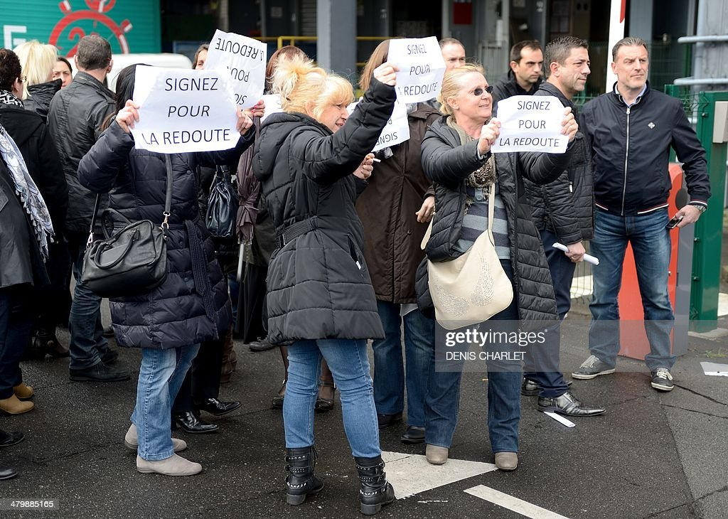 Employees of the French retail company 'La Redoute' demonstrate in favor of the compensations proposed by the direction for laid-off workers while others employees (unseen) protest against layoffs on March 21, 2014 in front of the company's headquarters in Roubaix, northern France. The new company owners announced they were planning on laying off 1.178 out of the 3.437 employees currently hired at the La Martinoire à Wattrelos factory site.