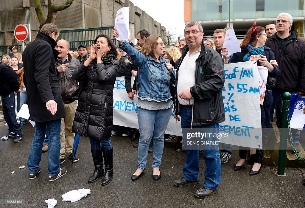 Employees of the French retail company 'La Redoute' take part in a protest against layoffs while others employees (unseen) demonstrate in favor of the compensations for laid-off workers proposed by the direction on March 21, 2014 in front of the company's headquarters in Roubaix, northern France. The new company owners announced they were planning on laying off 1.178 out of the 3.437 employees currently hired at the La Martinoire à Wattrelos factory site.