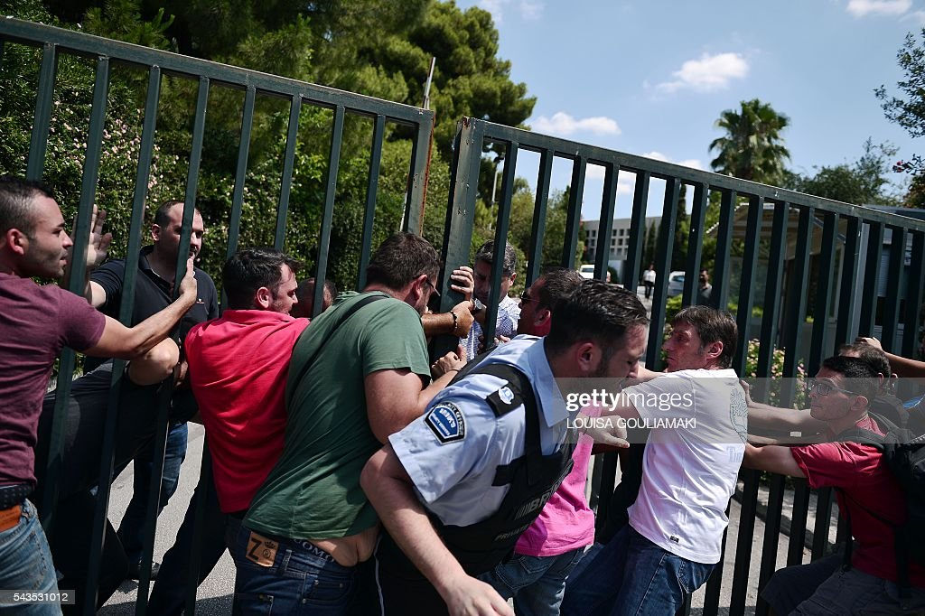 Employees of the Greek largest retail chain Marinopoulos, Carrefour's franchise partner in Greece and some Balkan countries, try to break into the company's headquarters in southern Athens on June 29, 2016 after the company filed for protection from its creditors, under the threat of confiscations. Marinopoulos, Greeces biggest supermarket chain, is on the verge of bankruptcy. If its application is rejected some 12,500 employees will be left jobless and over 2,000 suppliers and creditors will lose money, creating an unprecedented situation in the Greek market. / AFP / LOUISA
