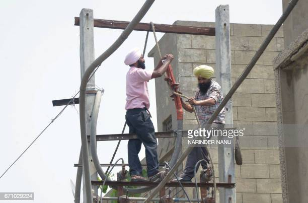Employees of the Indian Punjab State Power Corporation repair an electric pylon in Amritsar on April 21 2017 Electricity cuts are common across...