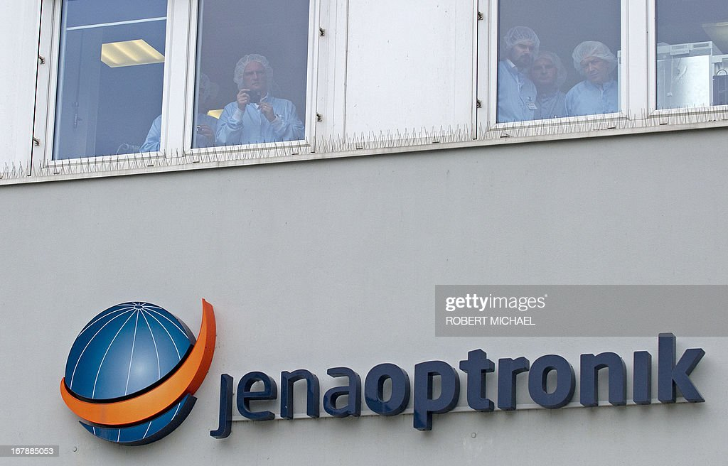 Employees of the Jena-Optronik GmbH (Ltd), a provider of opto-electronic instruments and sub-systems for space applications, look out from a window during the vistit of the German Chancellor on May 2 , 2013 in Jena, eastern Germany. AFP PHOTO / ROBERT MICHAEL