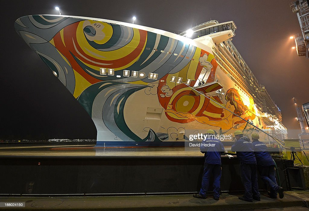 Employees of the Meyer Werft shipyard watch the Norwegian Norwegian Getaway cruise before being pulled by tugboat down the Ems river towards the...