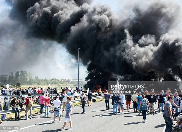 Employees of the MyFerrylink company stage a protest by blocking the A16 highway with a tyre fire in Calais on July 21 2015 The power struggle...