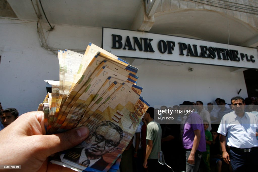 A Employees of the Palestinian Authority shows the money he withdrew from an ATM in the Rafah in the southern Gaza Strip on June 11 2014 Palestinian...