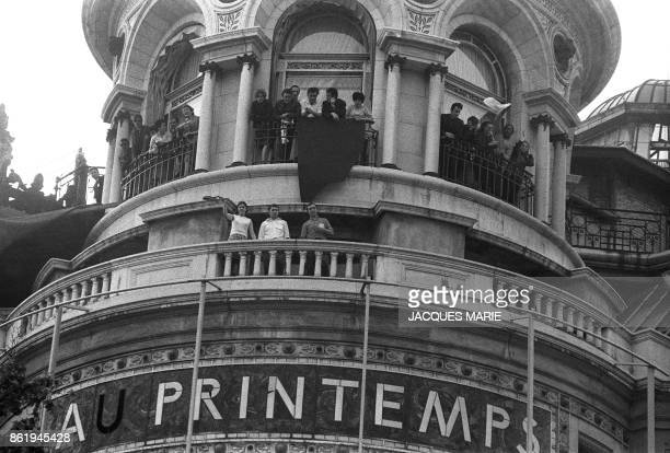 Employees of the Paris department store 'Le Printemps' who are on strike hang a red flag from a balcony on top of the store 29 May 1968 as they watch...