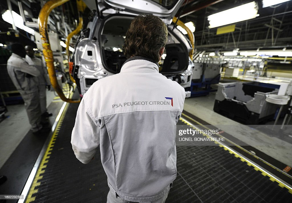 Employees of the PSA Peugeot Citroen carmaker plant of Aulnay-sous-Bois, a Paris' suburb, are at work on the assembly line on January 28, 2013 in Aulnay-sous-Bois. AFP PHOTO LIONEL BONAVENTURE