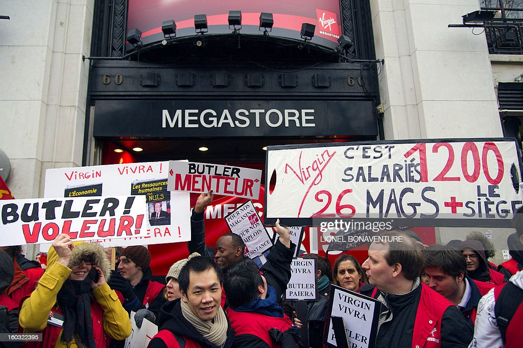 Employees of the retailer Virgin France Megastore demonstrate in front of the store on the Champs-Elysees avenue, on Juanuary 29, 2013 in Paris. Megastore music and book unit, which is known in France as a 'culture' retailer, said two weeks ago it will file for insolvency. Originally started by Richard Branson, the British billionaire and chairman of the Virgin Group, the Virgin megastores were bought by the French Lagardere group in 2001 before French-American businessman Walter Butler became the majority shareholder. Butler announced on January 20, 2013, its failure to relaunch the stores. The banners read : 'Virgin will leave, Butler has to pay !' (at left and foreground) and 'Butler liar' at center..