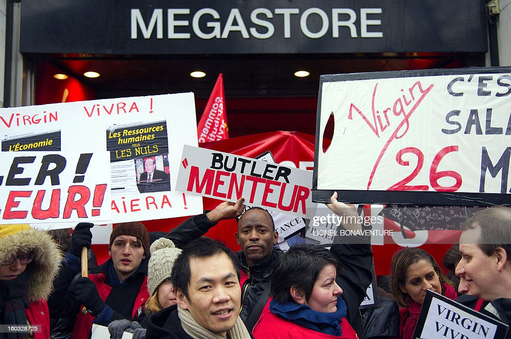 Employees of the retailer Virgin France Megastore demonstrate in front of the store on the Champs-Elysees avenue, on Juanuary 29, 2013 in Paris. Megastore music and book unit, which is known in France as a 'culture' retailer, said two weeks ago it will file for insolvency. Originally started by Richard Branson, the British billionaire and chairman of the Virgin Group, the Virgin megastores were bought by the French Lagardere group in 2001 before French-American businessman Walter Butler became the majority shareholder. Butler announced on January 20, 2013, its failure to relaunch the stores. The banner at center reads : 'Butler liar'. AFP PHOTO / LIONEL BONAVENTURE